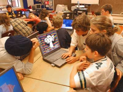 children looking at computer in classroom