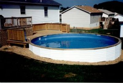 Medallion St. Croix above ground swimming pool installed into a hillside with vinyl siding, wood top cap, and wood deck.