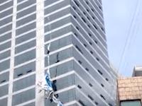 韓国で高層ビル外壁の大型懸垂幕の取り外し作業をしていた男性が死にかけている動画。