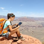 Tablet computer woman hiking in Grand Canyon using travel app or map during her hike. Multiethnic hiker girl relaxing on South Kaibab Trail, south rim of Grand Canyon, Arizona, USA.