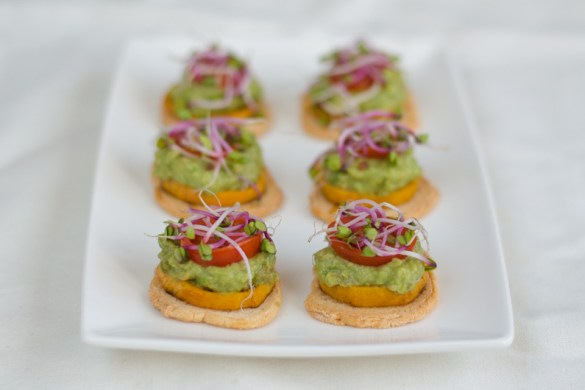 Sweet Potato and Avocado Bites are small round melba toasts with a slice of baked sweet potato, mashed avocado, half of cherry tomato and radish sprouts.
