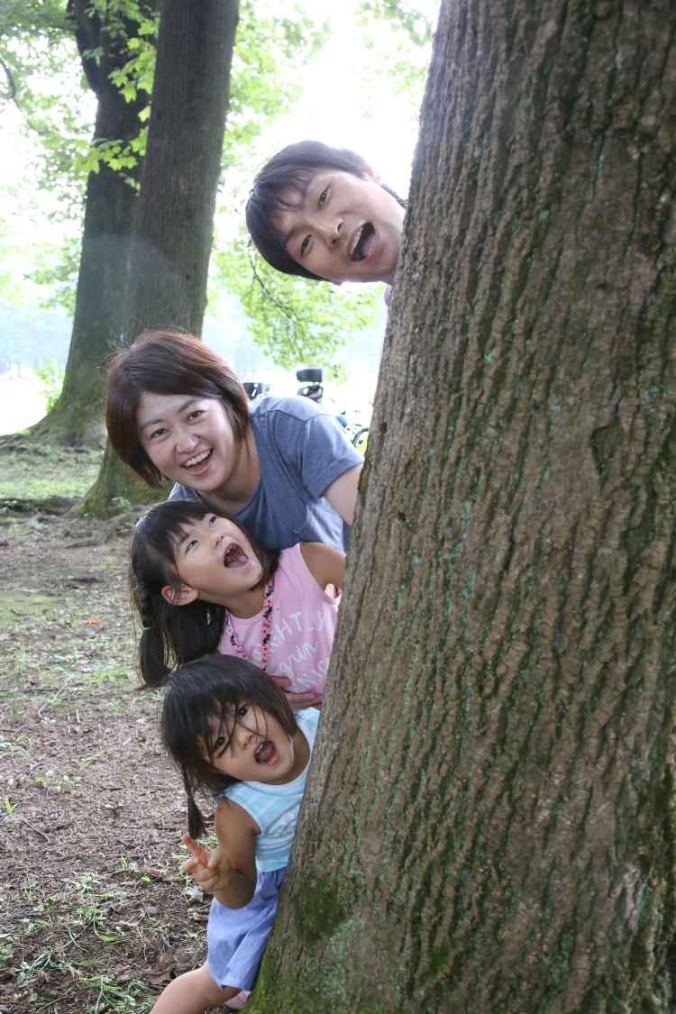木に隠れて遊ぶ家族
