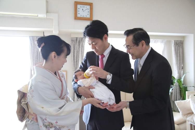 ご自宅でミルクを飲む赤ちゃんと見守る家族