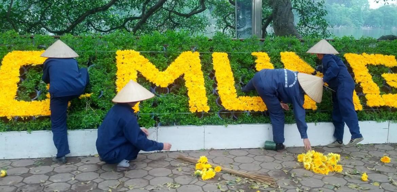 Arbeiterinnen pflanzen einen Blumenschriftzug in Hanoi. Foto: Frederic Spohr