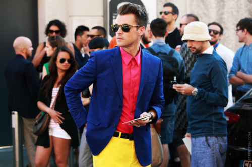 Man in blue jacket, yellow pants and pink shirt