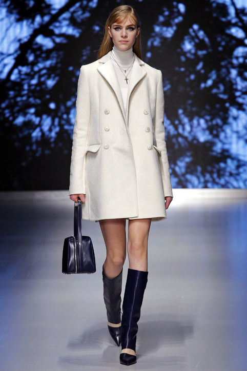Model walking runway in white winter coat