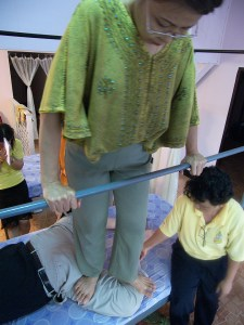 SomaVeda Thai Yoga incorporates the Anantasuk Walking method. Here grandma gives Dr. Anthony James a treatment in the Fa Meung position. Notice the low bar! In our system we want the body support system for walking to be low to properly support the body weight while walking on the client.