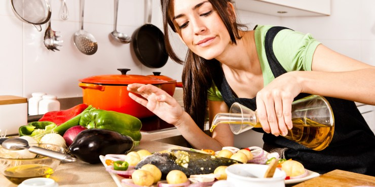 Woman pouring olive oil over fish