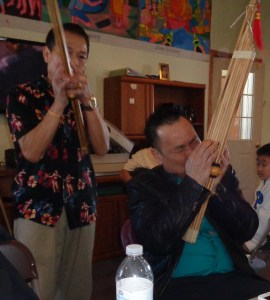 Hmong and Lao residents perform flute and keej music at the Warroad Buddhist Temple in Warroad, Minn. on March 20, 2016. (Photo by Jay Clark)