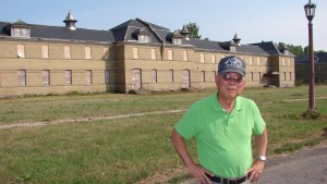 Edwin Nakasone Ph.D., an MISLS graduate in 1946, stands in front of the cavalry barracks of Fort Snelling in 2007.