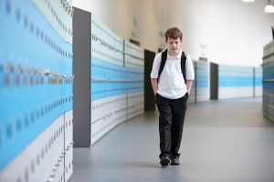 Unhappy schoolboy walking alone in school corridor