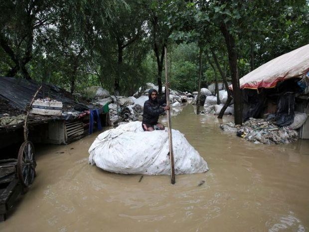 رجل يعتلي كيس ممتلئ بالزجاجات البلاستيكية عائم فوق الفيضانات التي غمرت أكواخ ومنازل المواطنين