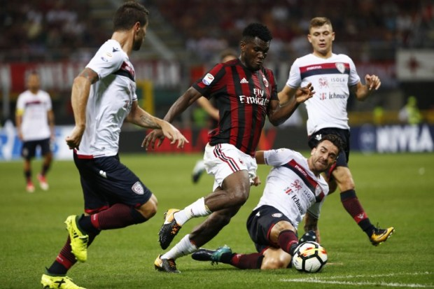 AC Milan's midfielder Franck Kessie from Ivory Coast (C) vies with Cagliari's defender Fabio Pisacane during the Italian Serie A football match AC Milan Vs Cagliari on August 27, 2017 at the 'Giuseppe Meazza' Stadium in Milan.  / AFP PHOTO / Marco BERTORELLO