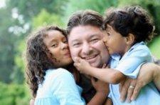 man and kids kissing his cheek