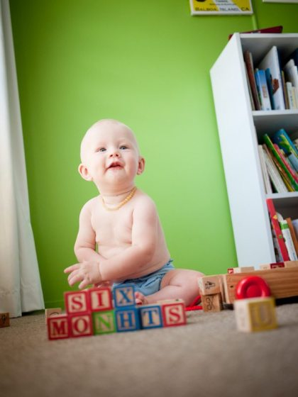 six month old baby boy playing with blocks