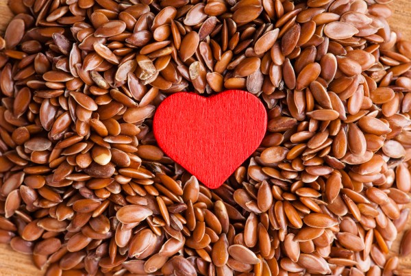 diet healthcare concept. Brown raw flax seeds linseed as natural background and red heart symbol. Healthy food for preventing heart diseases. Flaxseeds are full of omega-3 fatty acids.