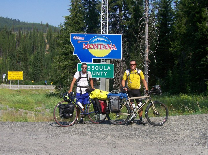 Cross country cyclists at the Montana border.