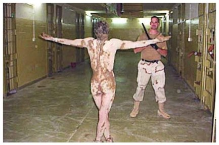 While his armed guard looks on and smiles, a detainee at Abu Ghraib in Iraq is covered with excrement and forced to parade for the camera.