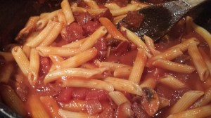 Add the cooked penne to the sauce and toss. (Photo Credit: Adroit Ideals)