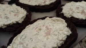 Spread the herbed cream cheese mixture on the pumpernickel slices (Photo Credit: Adroit Ideals)