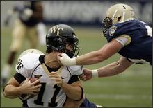 Wake Forest quarterback Riley Skinner almost lost his head in the monsoon this weekend in Annapolis, Md. (AP photo)