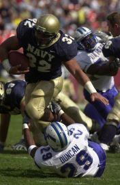 Kyle Eckel runs over an Air Force player during a 2003 game. ( Navy photo / JO1 Mark Faram)