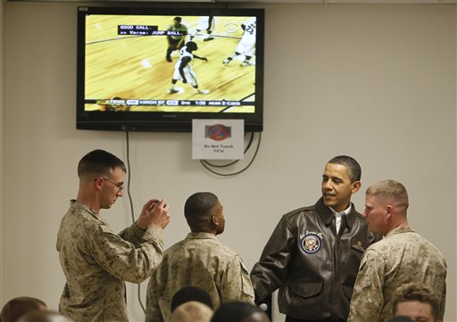President Obama greets military personnel in Dragon dining facility at Bagram Air Base on March 29. The Michigan State-Tennessee regional final is on TV in the background(AP Photo/Charles Dharapak)