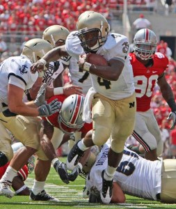 Navy's Ricky Dobbs, center, breaks through the line of scrimmage to score a touchdown against Ohio State during the first quarter of an NCAA football game Saturday, Sept. 5, 2009, in Columbus, Ohio. (AP Photo/Terry Gilliam)
