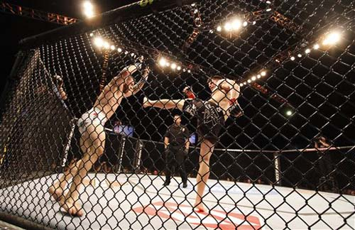 Brian Stann, right,  misses on a kick in his victory against Mike Massenzio at UFC on Versus 2. (AP Photo/Denis Poroy)