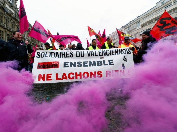"Demonstrators hold a banner reading ""together, we won't give in"" during a demonstration against the French government's proposed labour law reforms on March 31, 2016 in Valenciennes, northern France. Fresh strikes by unions and students are being held across France against French Labour minister's proposed reforms to France's labour laws, heaping pressure on President Francois Hollande who suffered a major defeat over constitutional reforms on March 30. / AFP / FRANCOIS LO PRESTI"