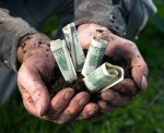 Man holding soil with dollars