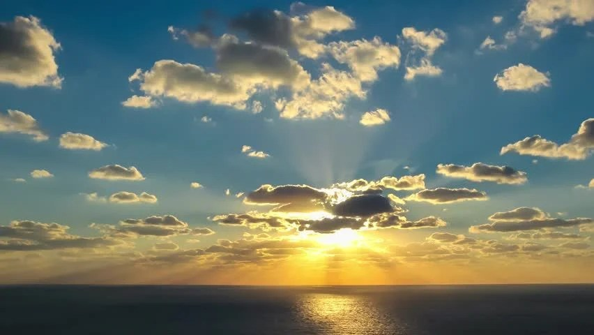 4k Timelapse Clouds Crossing The Amazing Sky Over The Sea Or Ocean At Sunset. Sun Rays Emerge ...