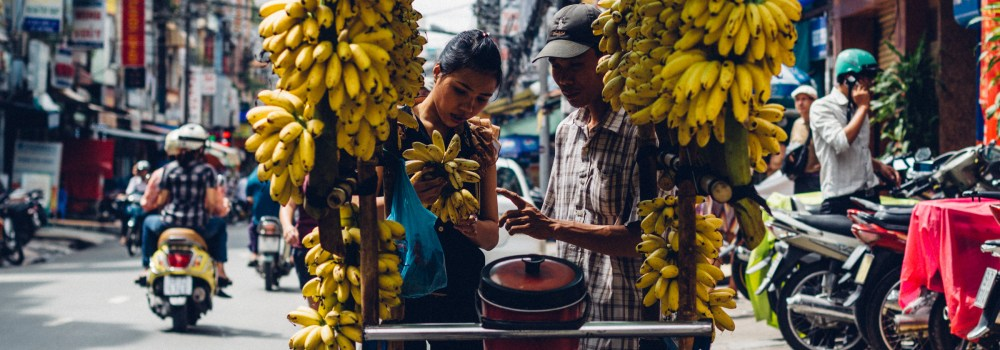 A mobile street seller finds a likely customer for his bananas (or are they more correctly called plantains?).