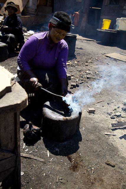 Woman cooking sheep's head, Langa Township, South Africa  (c) Allyson Scott