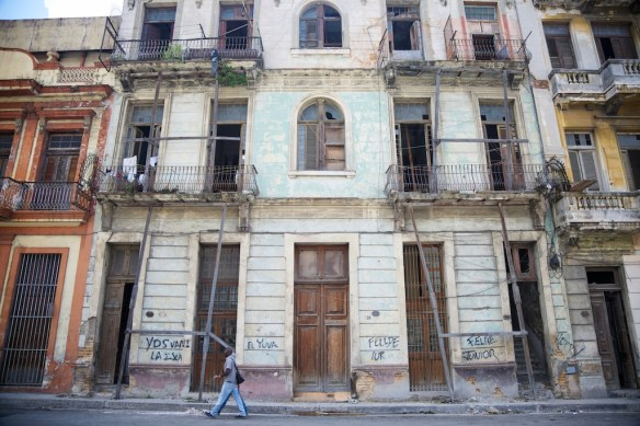 Badly damaged building in Havana with weathered supports