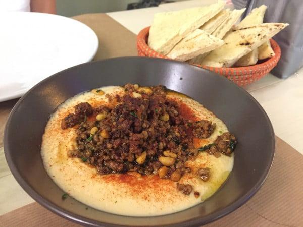 Hummus, merguez, piñones y pan de pita.