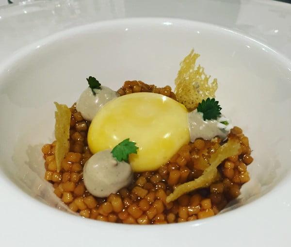 Huevo de caserío, guiso de trigo y jugo de pimientos a la brasa con pan de Mungia.