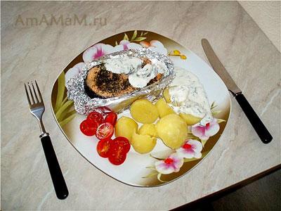 Тарелка очень вкусной еды: запеченный, очень сочный лосось, картошка, помидорки черри и соус для рыбы