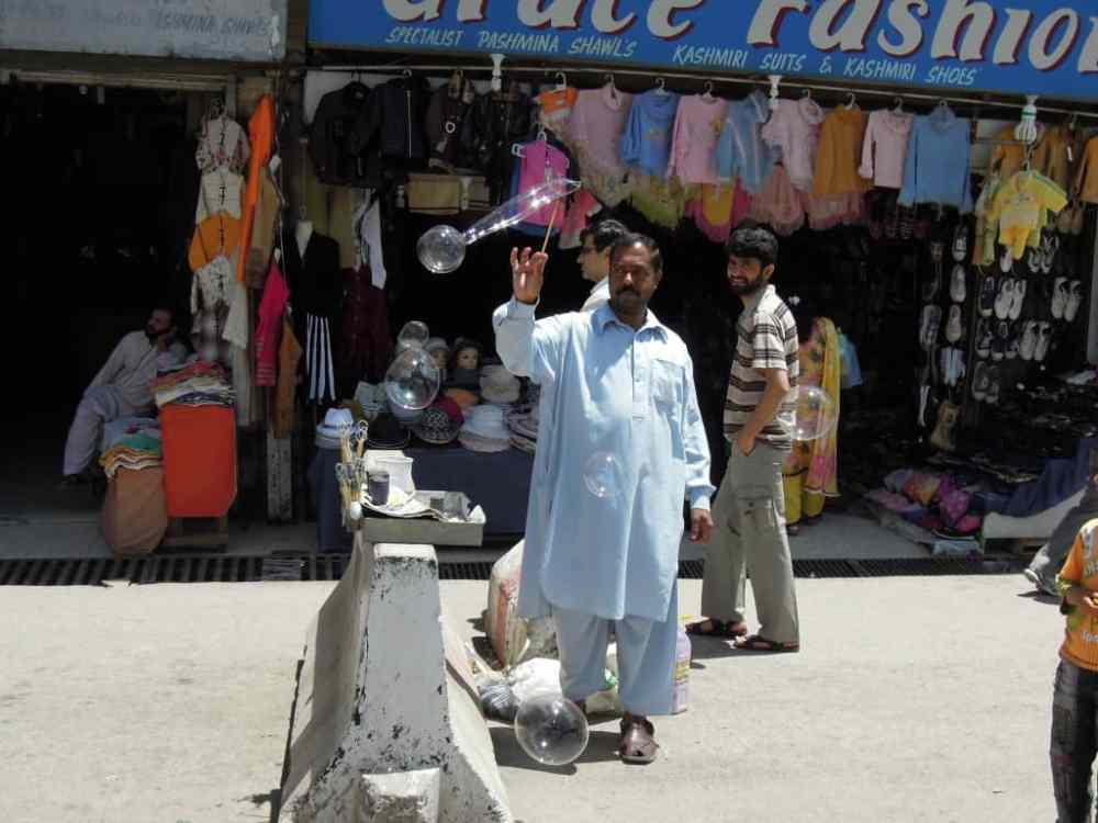 A Pakistani man uses a wand and solution to make bubbles in Murree, Pakistan