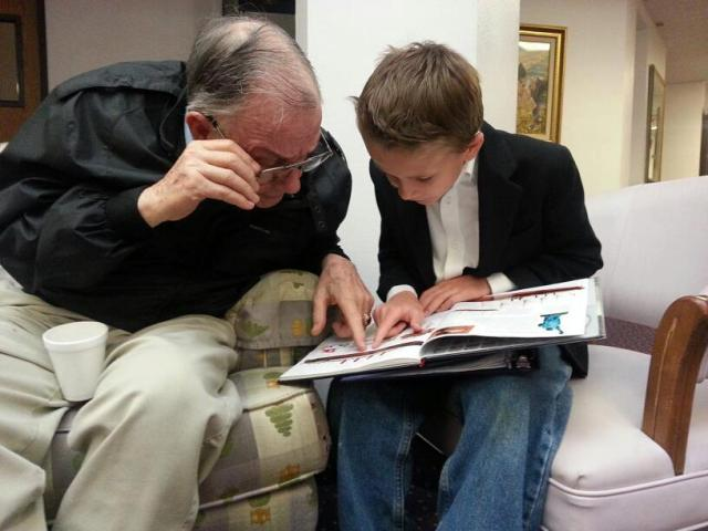 Nick reads about the Titanic with a resident at Lake Shore Commons Senior Living Center.