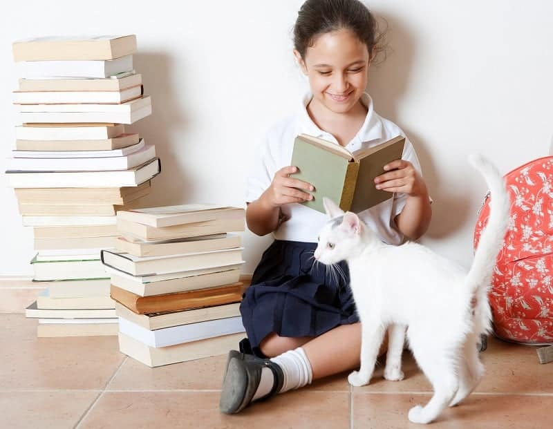 Young girl reading a book with her cat at home, sitting next to two piles of books.