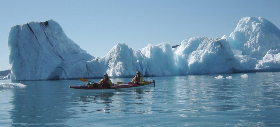 Floating through huge icebergs in kayak