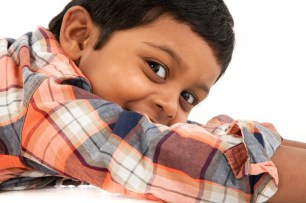 indian little boy studio photoshoot lying down checky smile