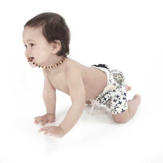 Toddler little boy crawling and chewing his necklace professional studio photography by Anais Chaine in Auckland Ponsonby New Zealand