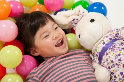 Asian little girl laughing with rabbit cuddly toy
