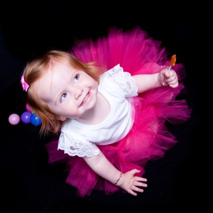 Pink ballerina dress on toddler, Auckland, Anais Chaine Stuido black background. Do you want my candy?