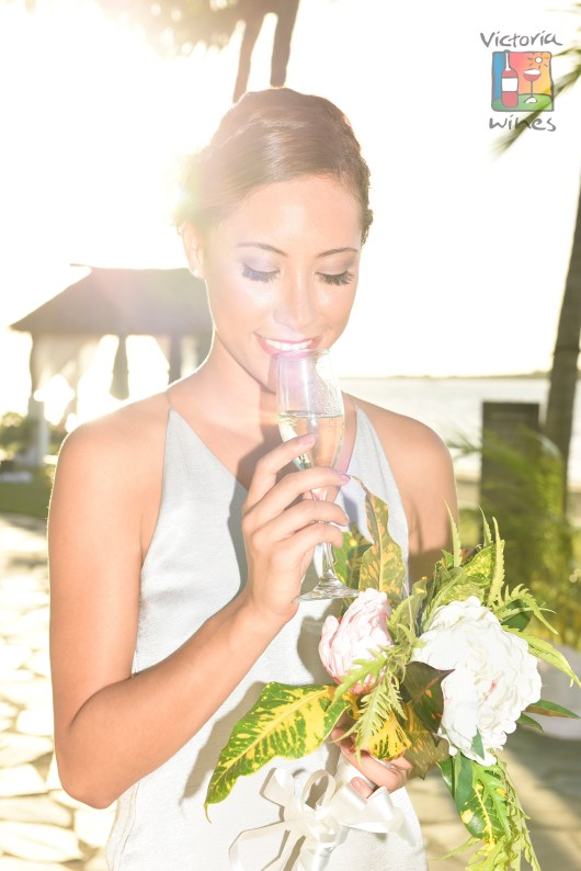 Portrait of a beautiful woman smiling and smelling a glass of white wine in her right hand and keeping a bouquet of flowers in her left hand Fiji Victoria Wines logo