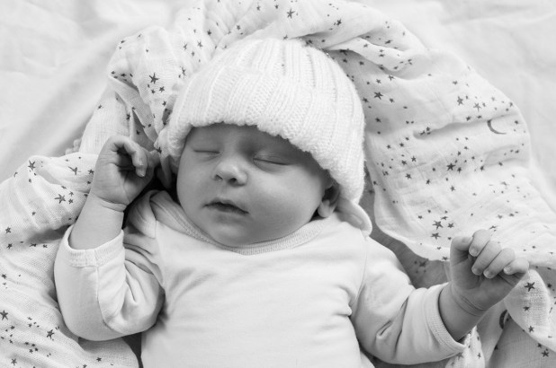 new born sleeping and wearing a bennie