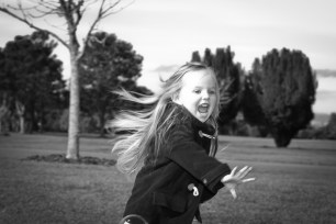 Professional portrait of young girl in movement black and white in One Tree hill Park, Auckland, New Zealand