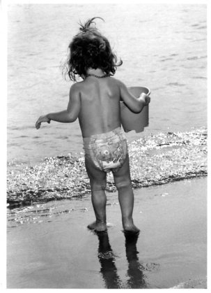 Little girl walking to the sea holding her bucket in Hyeres, south of France, French Riviera.